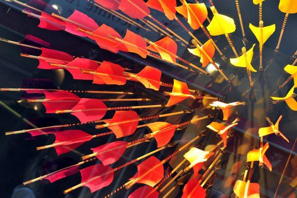 This photo shows darts stuck in a Plexiglas window