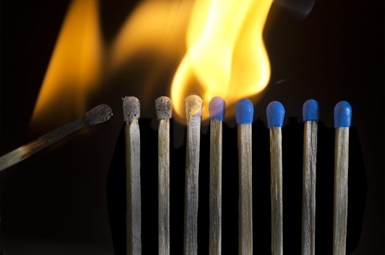 Starting the Fire. A line of match sticks stands bravely, as certain doom approaches.